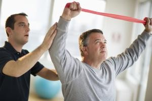USA, New Jersey, Jersey City, Fitness instructor assisting man in gym